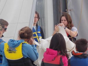 Olympia Yacht Club Junior Sailing Instructor Laura Smit (right) instructs campers on knot-tying skills as fellow instructor Liam Lloyd looks on (left).
