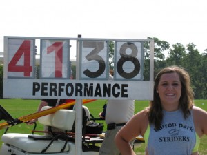 """As a junior, Northwest Christian High School's Karen Bulger stands next to her winning distance in the javelin  (in meters) at the National Junior Olympics in Baltimore, which was 135'9""""."""