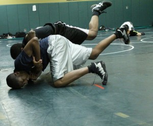 AJ Edwards (front) latches on to the wrist of his opponent Wayne Harris, who wrangles both into a backwards somersault.