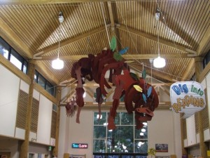 The Lacey Timberland Library branch offers an engaging and welcoming area for children and youth.  A giant dinosaur sculpture hangs from the ceiling, just one example of the libraries' efforts to create a fun and engaging, youth-friendly atmosphere.  Photo credit: Gale Hemmann