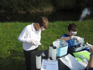 On Water Quality Monitoring Day, Kai Nicholas and Nicholas Heelan test water samples from the Deschutes River.