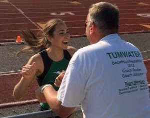 Tumwater High School's Peyton Russell celebrates with her coach after a successful jump.
