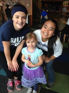 Jessica McGregor (left) and Hope Dorris smile with their preschool buddy Madison at Hands On Children's Museum.