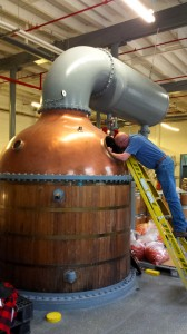 Bourdon, seen here inspecting the historic still-condenser, will modify it for use at Sandstone Distillery.