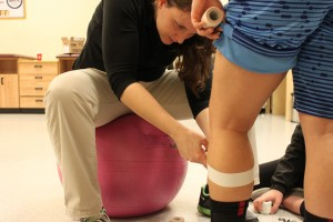 As an athletic trainer, Rebekah McFann  knows how to tape many body parts for added support during activities. Here, she tapes a student's knee.