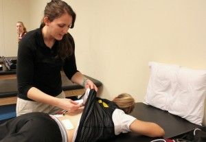 There's more to athletic training than just taping. Rebekah McFann uses an E-stem machine on an athlete's back, to provide pain relief from aching muscles.
