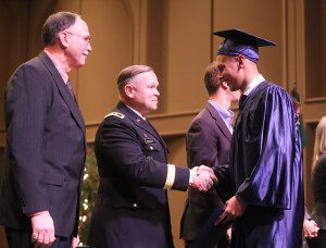Alec Frazier of Rochester shakes the hand of Major General Bret D. Daugherty of the Washington National Guard during commencement proceedings on December 19.