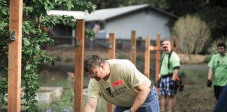 Rebuilding Together Thurston County Pete Kmet raking long wide shot