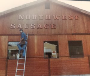 Northwest Sausage & Deli Dick putting up sign