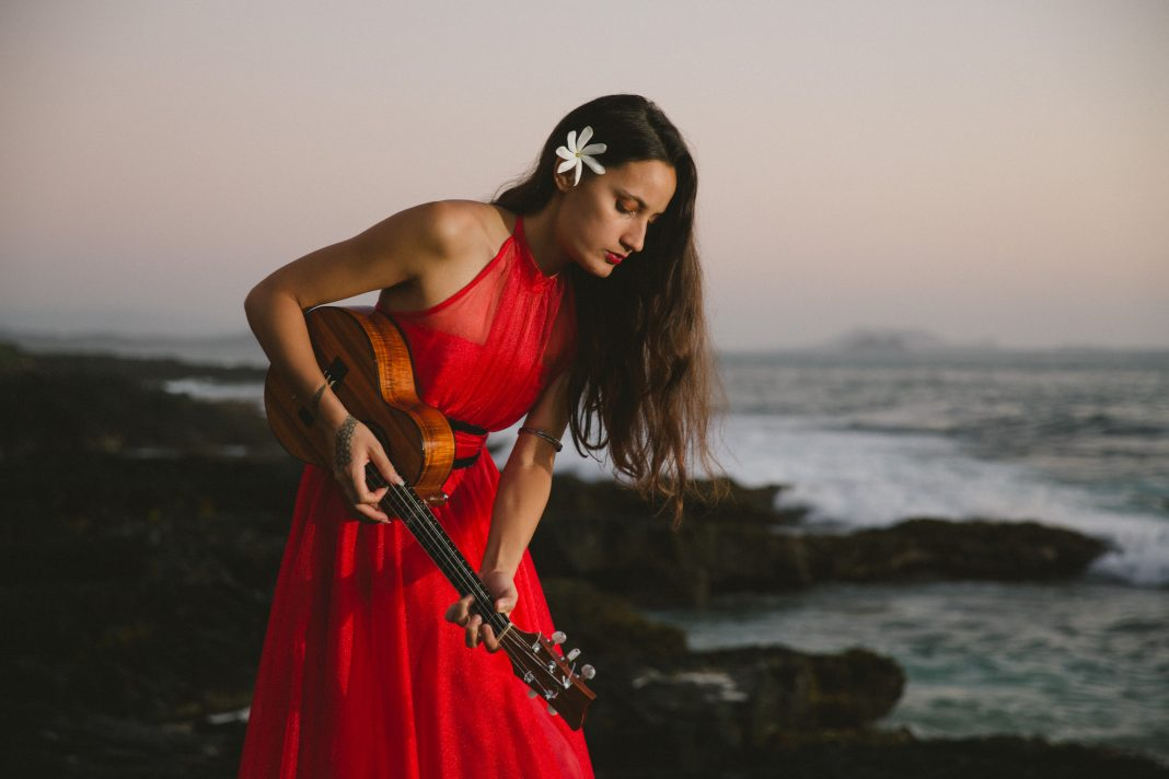 Taimane performing on beach in red dress