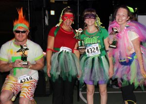 Glow in the Dark 5k four runners posing with trophies