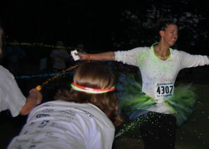 Glow in the Dark 5k partipant getting splashed with color
