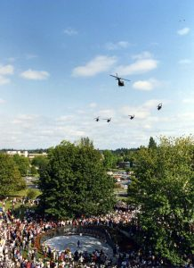 """A group of Army helicopters fly in a """"missing man"""" formation over the 1987 dedication of the Vietnam Veterans Memorial. The pilots were Vietnam veterans."""